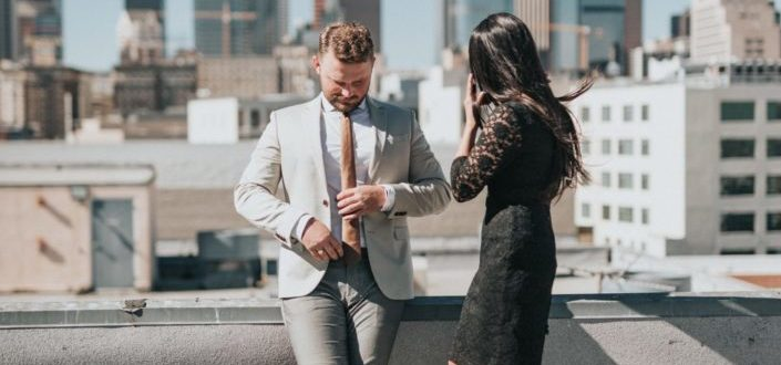 A well-dressed couple standing on a rooftop