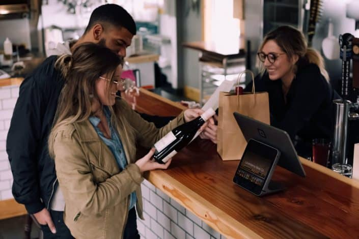 A couple paying for a bottle of wine