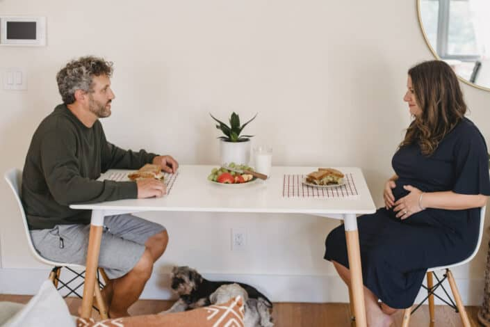 Mature couple eating lunch on dining table with dog below them.