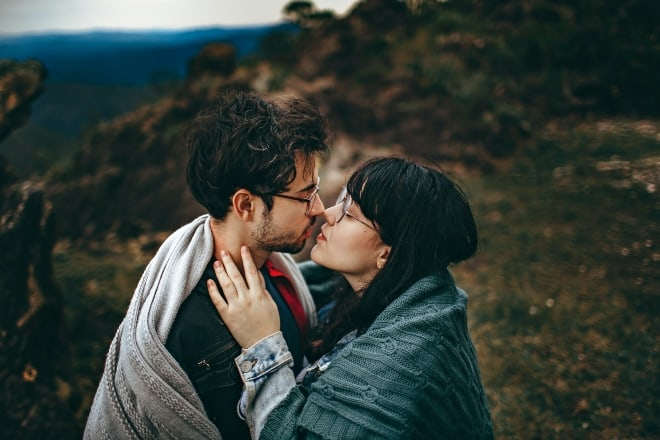 Couple sharing a kiss on a hill - How to kiss a guy