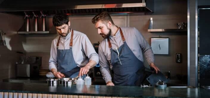 Two guys cooking together.
