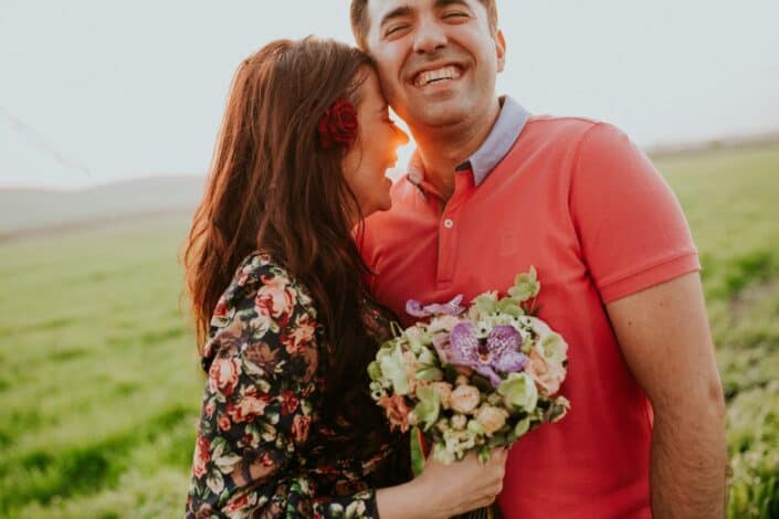 Couple smiling while holding a bouquet