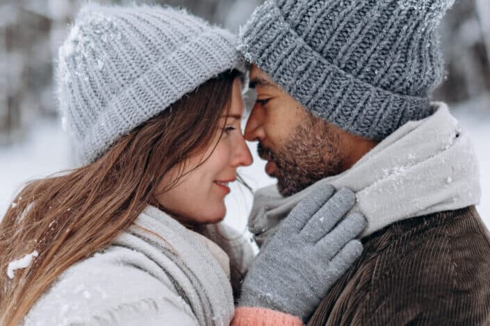 Couple about to kiss in snow.