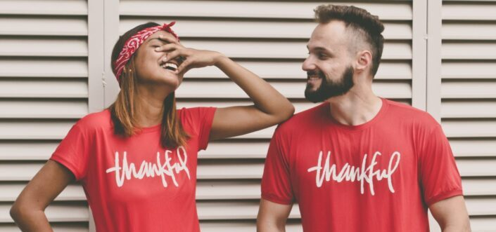 Couple wearing matching thankful red shirts smiling at each other.