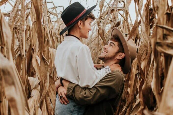 Guy lifting up a girl in a tall field.