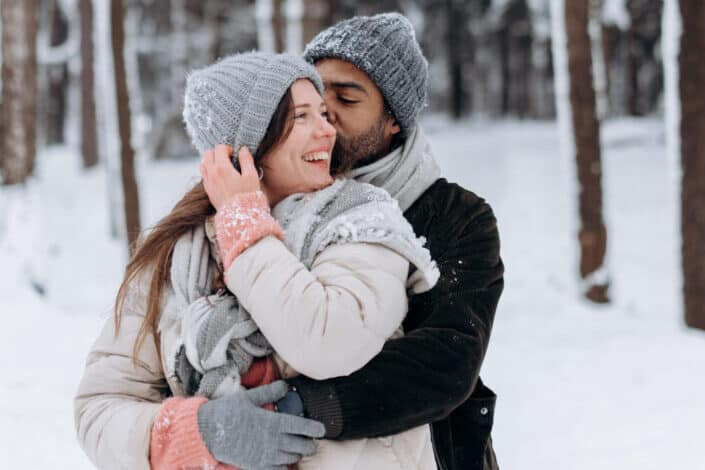Guy embracing a girl in snow.