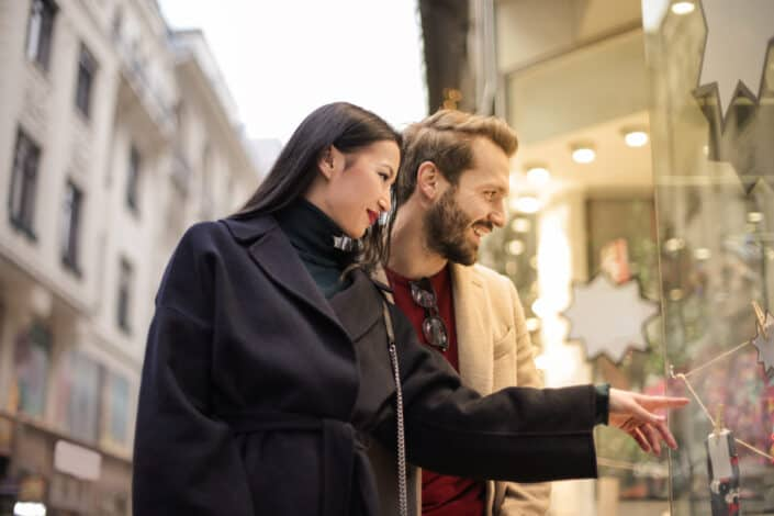 Girl pointing to a display window and guy smiling.