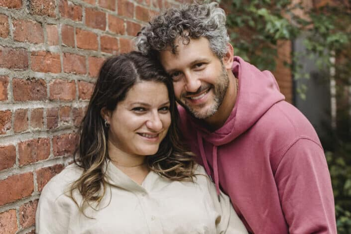 Mature couple smiling next to a brick wall.