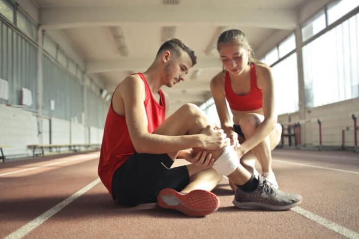 Girl helping guy teammate bandage his leg.