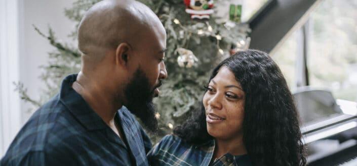 Positive black couple standing close near fir tree