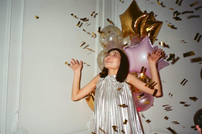 Girl celebrating with poppers and balloons.