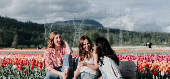 three women sitting on a bench near flowers