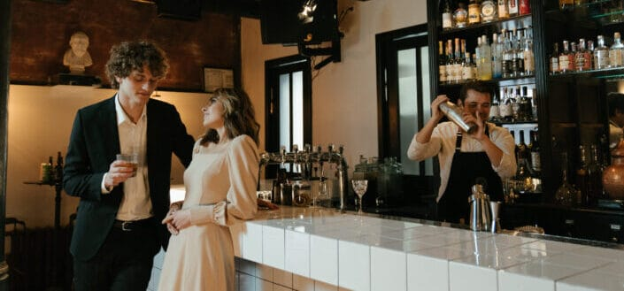 A couple talking beside a bar