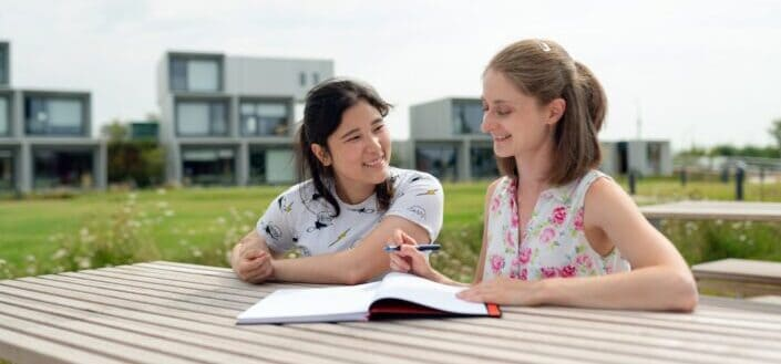 Two girls sitting on a park bench reviewing notes