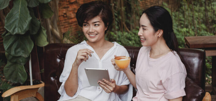 Two girls smiling while holding a cup of coffee and a tablet