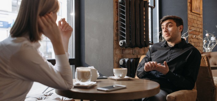 Two people discussing inside coffee shop