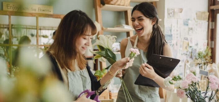 Two girls having fun at a flower store