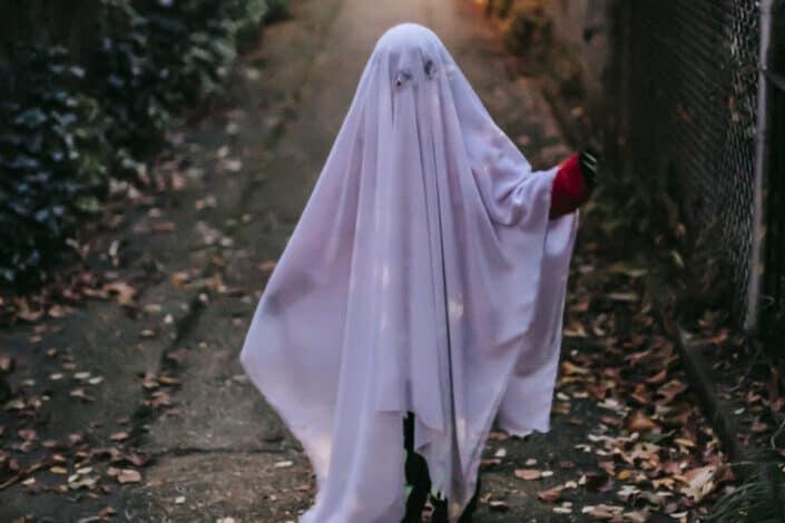 Little girl wearing a white blanket as Halloween costume