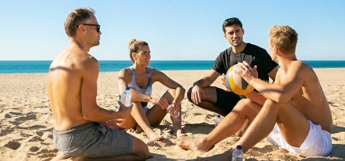 Group of people sitting on sand