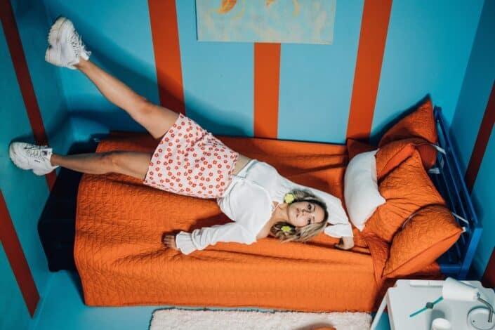 Girl lying down on orange bed