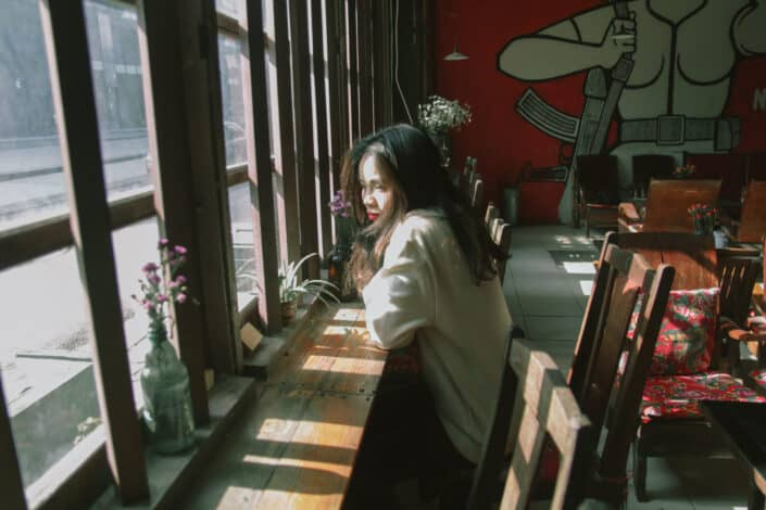 Girl sitting on a coffee ledge and staring out the window