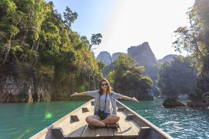 Girl sitting on small wooden boat and holding out her arms