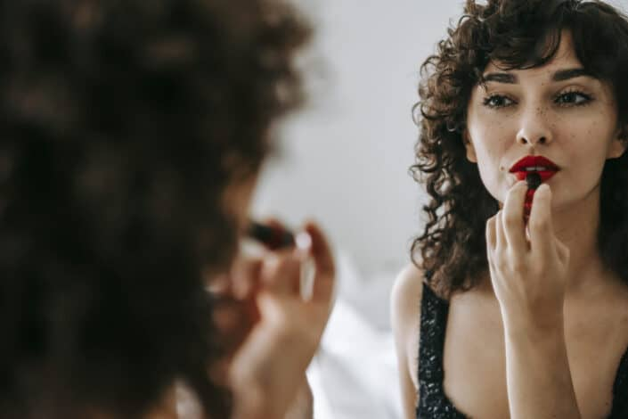Woman facing mirror and applying red lipstick