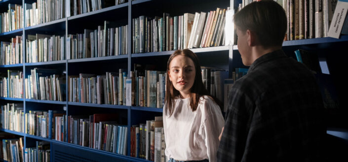 Two people standing near bookshelves