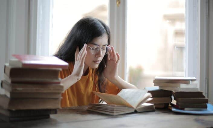 Girl trying to memorize with piles of books in front of her