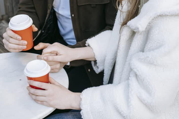 Cropped couple holding hands while holding coffee