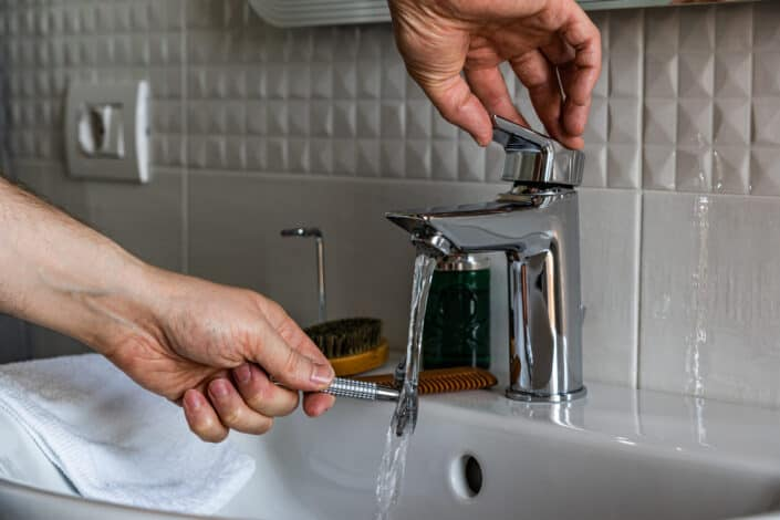 A man washing his shave under the faucet
