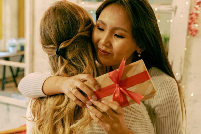Two women hugging each other while one holds a gift