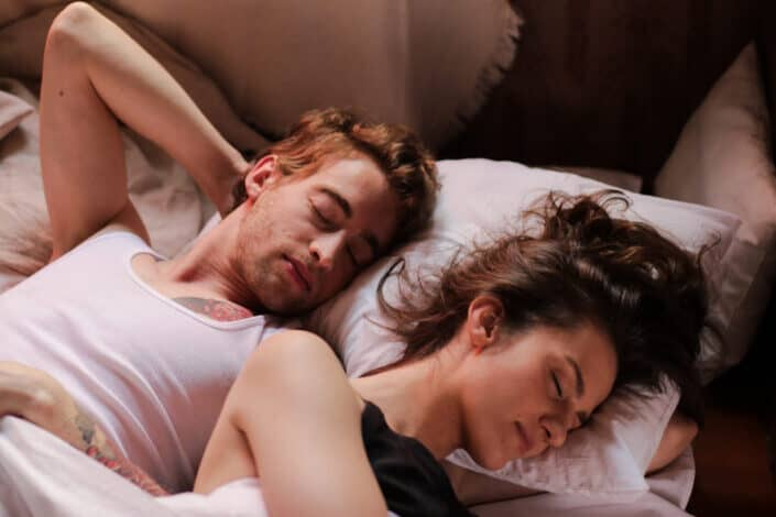 A couple sleeping on the same bed