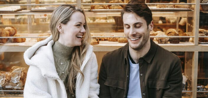 couple holding hands during date in bakery