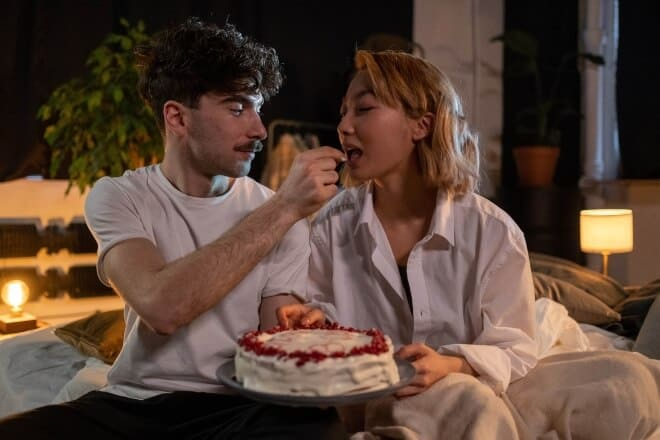 A man giving a woman a piece of a cake - flirty would you rather questions
