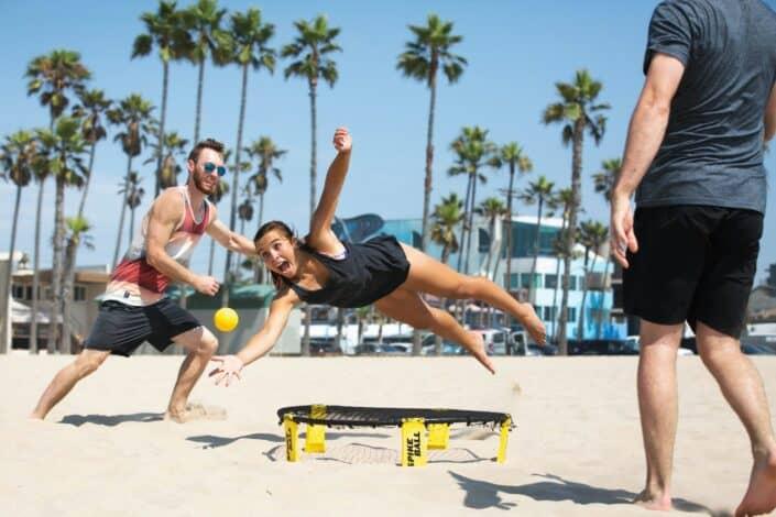 Girl diving for ball on beach