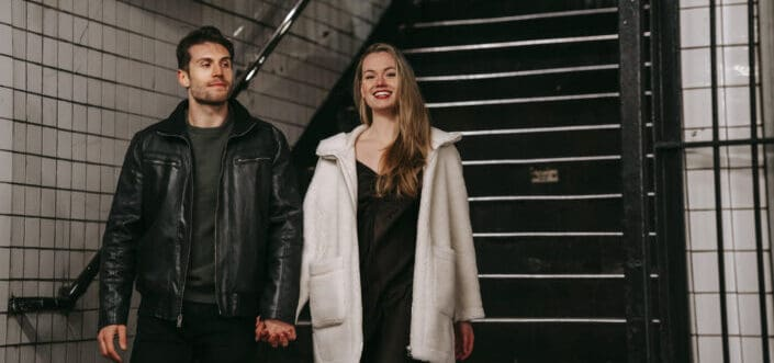 positive couple going downstairs in underground passage