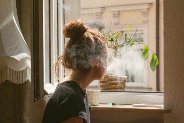 woman smoking while looking through the window
