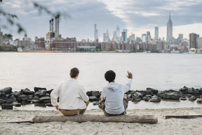 two men sitting on a log