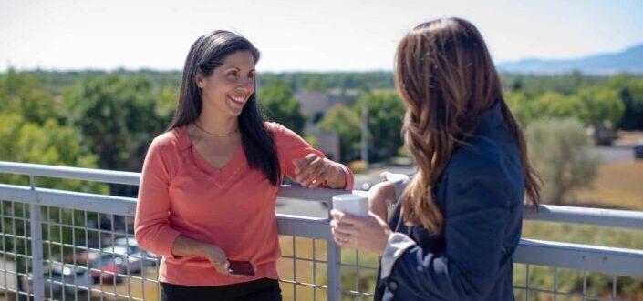 Two women talking in a rooftop.