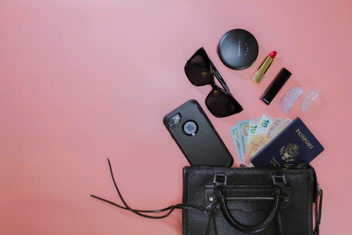 women essentials scattered from black leather pouch