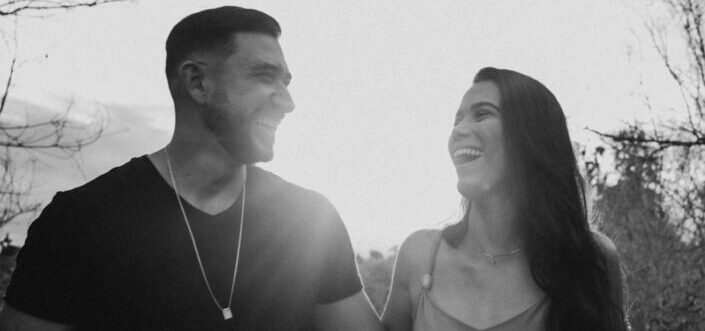 grayscale photo of couple laughing under daytime