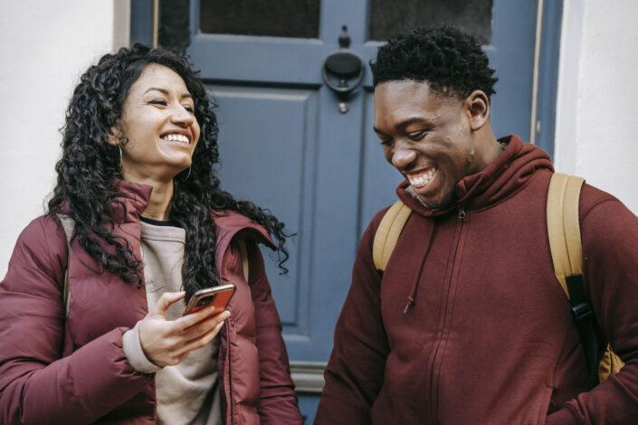 Friends with smartphones laughing near door of building