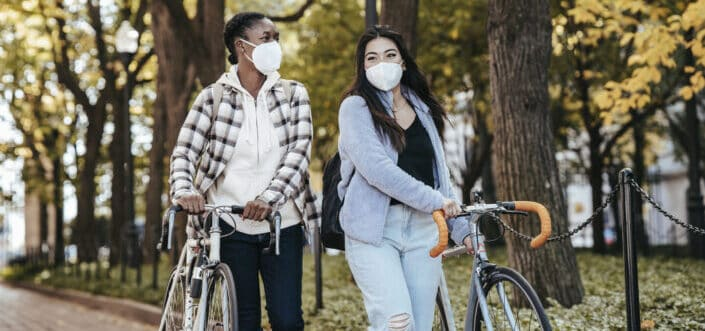Diverse girlfriends with bike walking on a pavement