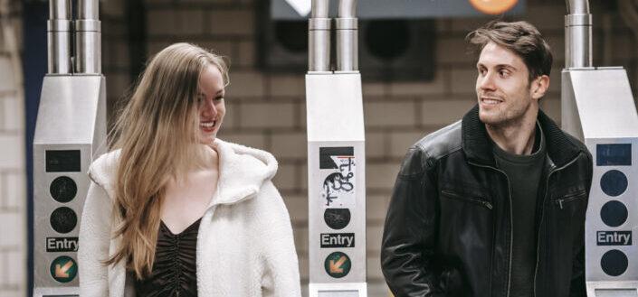 Happy couple walking through turnstile in underground