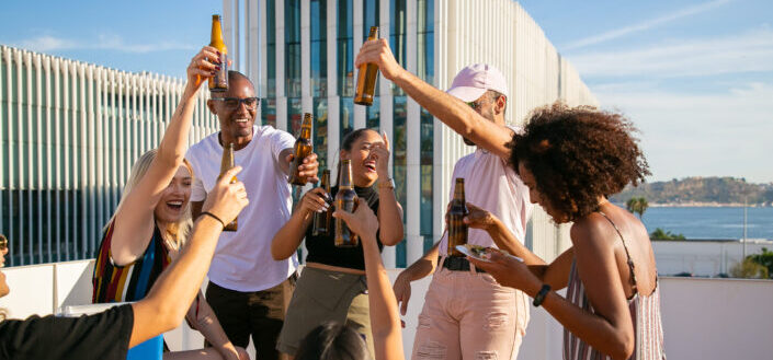 Joyful group of friends toasting with beer bottles on rooftop