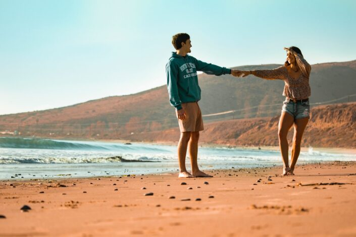 couple holding hands at seashore during daylight