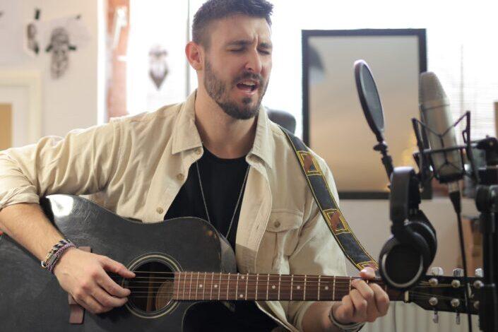 Man in brown button up shirt playing guitar