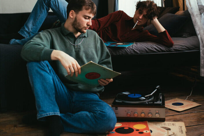 Two friends listening to vinyl records