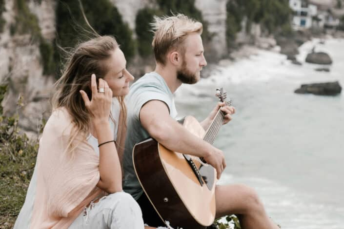 Peaceful young couple playing guitar on hill